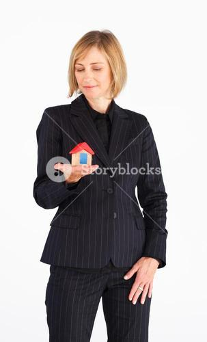 Selfassured mature businesswoman holding a house