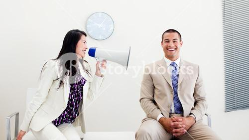 Furious businesswoman yelling through a megaphone at a colleague