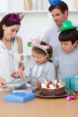 Cute girl unpacking Birthday presents with her family