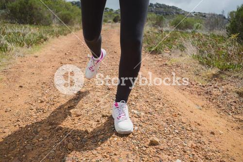 Low section of woman running on country road
