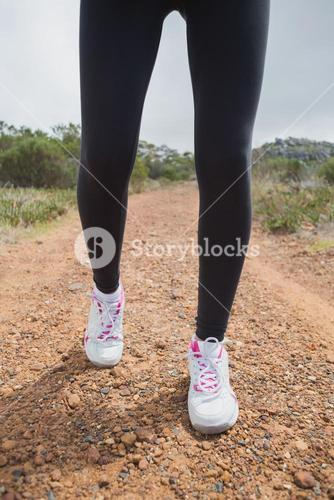 Low section of woman walking on country road