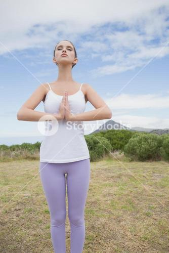 Woman with hands joined standing on countryside landscape