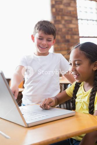 Cute little pupils looking at laptop in classroom
