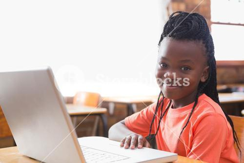 Cute pupil using laptop in classroom