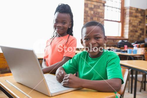 Cute pupils using laptop in classroom