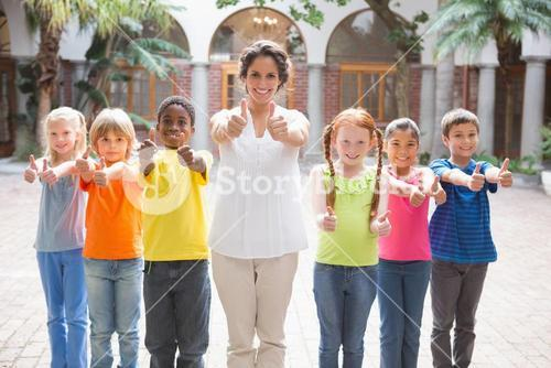 Pretty teacher standing with pupils in courtyard
