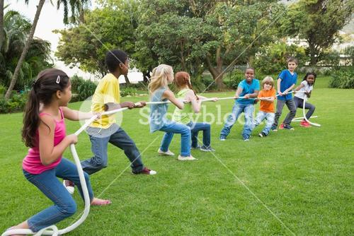 Cute pupils playing tug of war on the grass outside