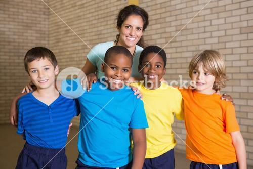 Cute pupils smiling at camera with PE teacher