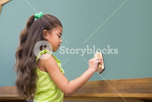 Cute pupil standing in classroom dusting chalkboard