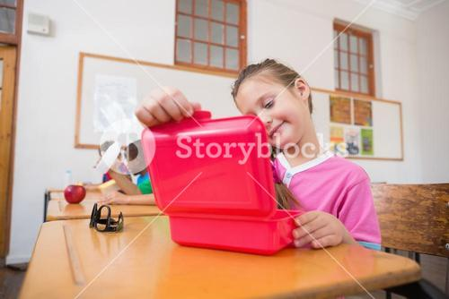 Cute pupil opening lunchbox at desk in classroom
