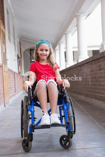 Cute disabled pupil smiling at camera in hall