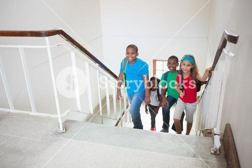 Cute pupils smiling and walking up stairs