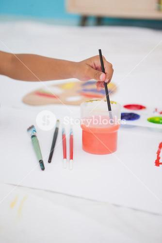 Cute little boy painting on floor in classroom