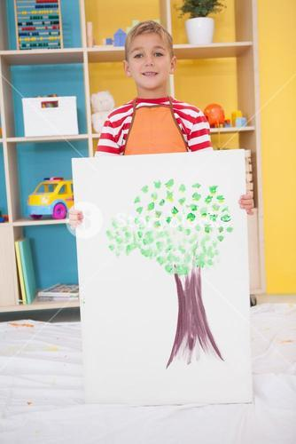 Cute little boy showing his painting in classroom