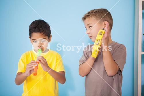 Cute little boys playing musical instruments in classroom
