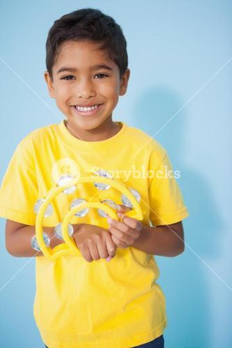 Cute little boy playing the tambourine in classroom