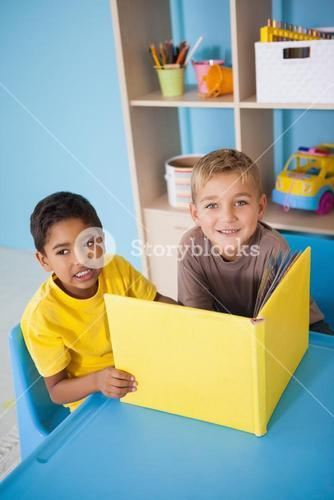 Cute little boys reading at desk in classroom
