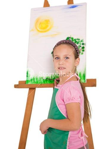 Happy little girl painting on easel