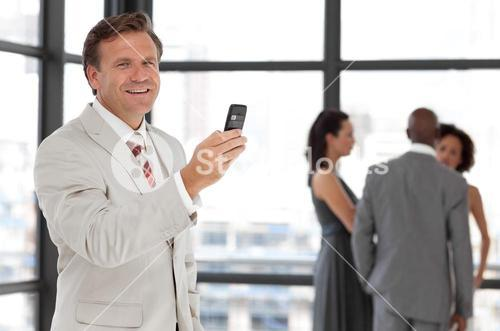 Charismatic businessman holding a phone at workplace with his colleagues
