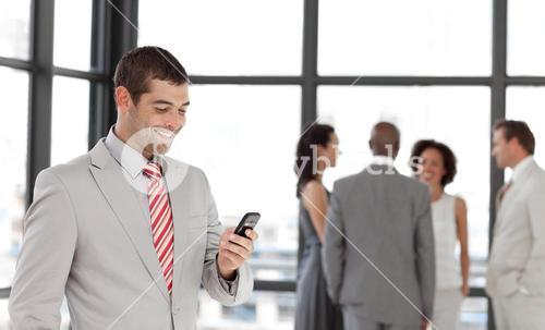 Latin businessman holding a phone at workplace with his colleagues