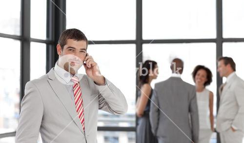 Serious businessman holding a phone at workplace with his colleagues