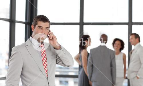 Selfassured businessman holding a phone at workplace with his colleagues