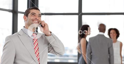 Young businessman holding a phone at workplace with his colleagues
