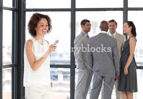 Businesswoman holding a phone at workplace with his colleagues