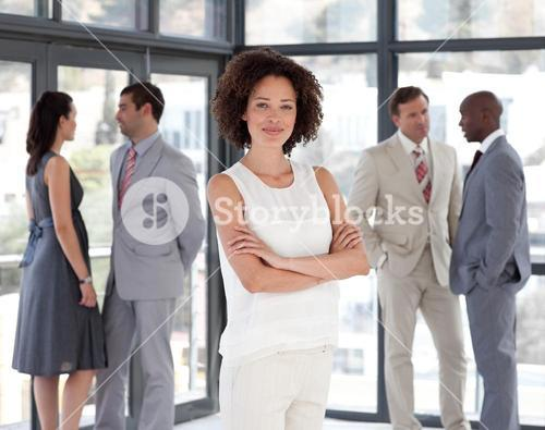 Beautiful businesswoman arms folded with his colleagues