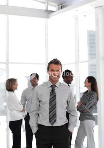 Young business manager standing at the camera with his team