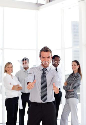 positive business manager standing at the camera with his team