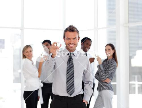 Attractive business manager holding a glass with his team