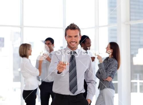 Happy business manager holding a glass with his team