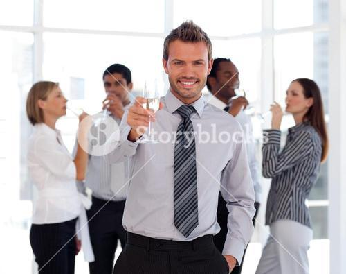Charming business manager holding a glass with his team