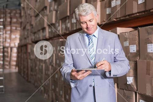 Warehouse manager writing on clipboard