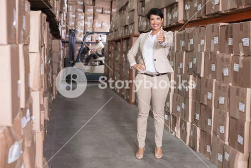 Pretty warehouse manager smiling at camera showing thumbs up