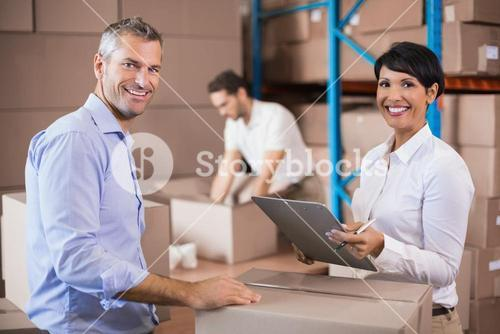 Warehouse manager writing on clipboard talking to colleague