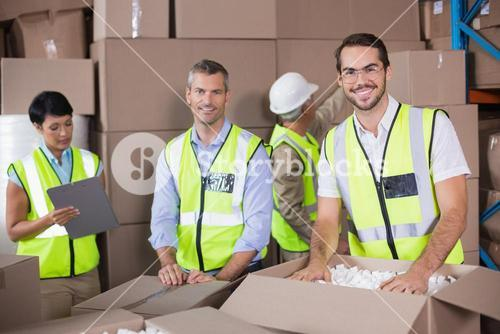 Warehouse workers in yellow vests preparing a shipment