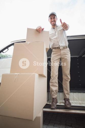Delivery driver smiling at camera in his van