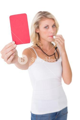 Young woman blowing whistle and holding red card