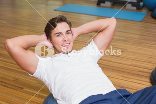 Man doing sit up on exercise ball