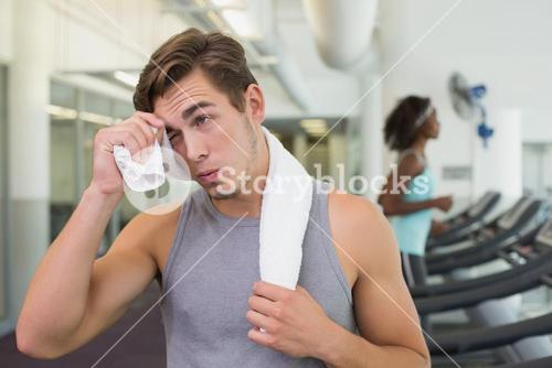 Handsome man wiping his forehead beside treadmills
