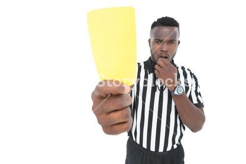 Serious referee showing yellow card