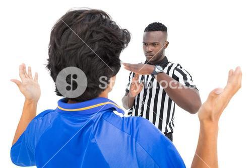 Serious referee showing time out sign to player
