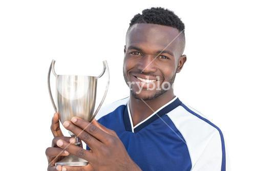 Football player holding winners cup