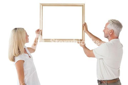Mature couple hanging up picture frame