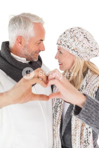 Mature couple forming heart with hands