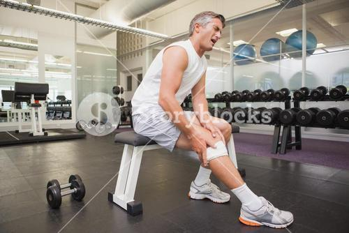 Injured man gripping his knee in the weights room