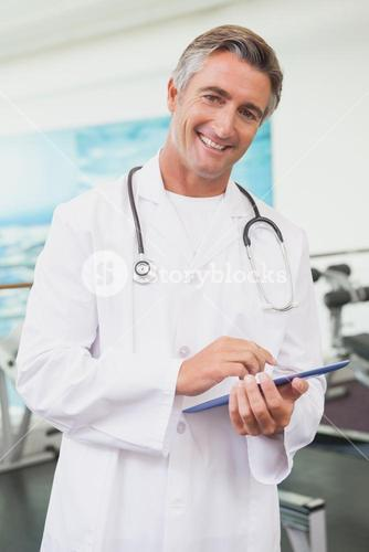 Confident doctor standing in fitness studio using tablet pc