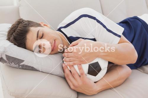 Football fan sleeping with ball